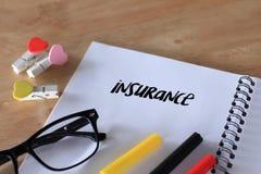 Escrita da palavra do seguro no caderno na tabela de madeira Imagem de Stock Royalty Free