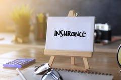 Escrita da palavra do seguro no caderno na tabela de madeira Imagens de Stock
