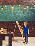 Escrita de Little Boy no quadro Criança da vista lateral na frente da placa verde com equação da matemática Estudo companheiro pe fotos de stock royalty free