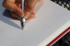 Escrita de prata da pena em um bloco de notas com uma mão do ` s da senhora na capa imagens de stock royalty free