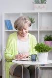 Escrita de sorriso da mulher no caderno imagem de stock royalty free