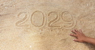 Escrita do ano na areia com alcance fora da mão do sobrevivente Imagens de Stock