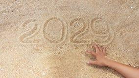 Escrita do ano na areia com alcance fora da mão do sobrevivente Imagem de Stock Royalty Free