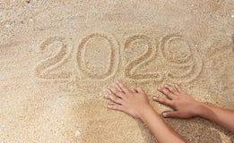 Escrita do ano na areia com alcance fora da mão do sobrevivente Fotos de Stock