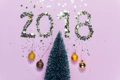 Escrita 2018 do ano novo composta de confetes de brilho sobre a árvore de Natal Fotografia de Stock Royalty Free