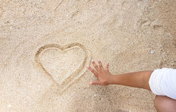 Escrita do coração na areia dourada com alcance fora da mão Foto de Stock Royalty Free