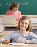 Escrita do estudante no caderno na sala de aula Imagem de Stock
