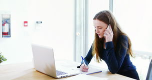 Escrita do executivo empresarial no diário ao falar no telefone celular vídeos de arquivo
