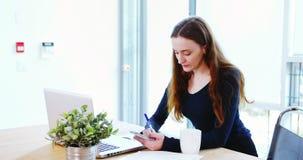 Escrita do executivo empresarial no diário ao olhar o portátil vídeos de arquivo