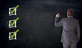 Escrita do homem de negócios com conceito da caixa de seleção no quadro-negro imagem de stock royalty free
