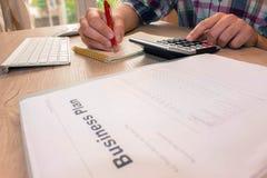 Escrita do homem de negócios em um caderno O funcionamento do homem determina Workspa Imagem de Stock Royalty Free