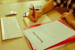 Escrita do homem de negócios em um caderno O funcionamento do homem determina Workspa Imagens de Stock Royalty Free
