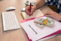 Escrita do homem de negócios em um caderno O funcionamento do homem determina Workspa Foto de Stock