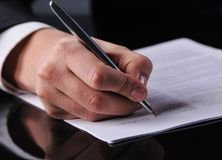 Escrita do homem de negócios em um formulário Fotos de Stock Royalty Free