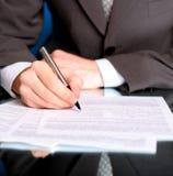 Escrita do homem de negócios em um formulário Imagens de Stock Royalty Free