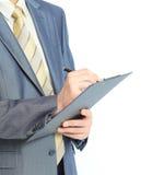Escrita do homem de negócios na prancheta isolada sobre o fundo branco Foto de Stock Royalty Free