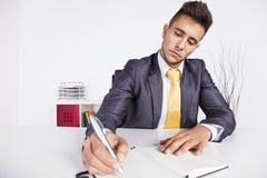 Escrita do homem de negócios no bloco de notas Fotos de Stock