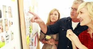 Escrita do homem de negócios no post-it e na foto com seus colegas filme