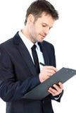 Escrita do homem de negócios no terno do desgaste da prancheta e no isola elegantes do laço Imagens de Stock