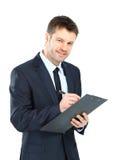 Escrita do homem de negócios no terno do desgaste da prancheta e no isola elegantes do laço Fotografia de Stock