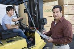 Escrita do homem em uma prancheta com o trabalhador que conduz Forktruck no armazém Fotos de Stock Royalty Free