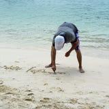 Escrita do homem na areia, praia de Langkawi Imagens de Stock