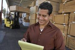 Escrita do homem no bloco de notas com o trabalhador que trabalha na empilhadeira no armazém Fotos de Stock