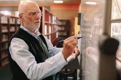 Escrita do homem superior na placa da sala de aula imagens de stock royalty free