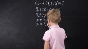 Escrita do menino na equação da matemática do quadro, resolvendo o exercício, reforma da educação video estoque