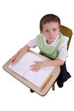 Escrita do menino na mesa da escola foto de stock royalty free