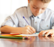 Escrita do menino no caderno foto de stock