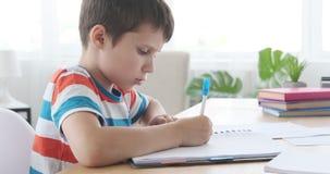 Escrita do menino no caderno em casa