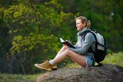A escrita do mochileiro da mulher nota a caminhada na floresta e no stopp do verão fotografia de stock