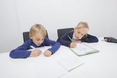Escrita do rapaz pequeno e da filha em originais na tabela Foto de Stock