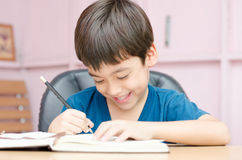 Escrita do rapaz pequeno e trabalhos de casa de pensamento imagem de stock