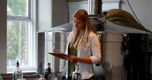 Escrita do trabalhador fêmea na prancheta na fábrica 4k da destilaria video estoque