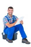 Escrita do trabalhador manual na prancheta ao sentar-se na caixa de ferramentas Fotografia de Stock Royalty Free