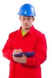 Escrita do trabalhador novo na prancheta Fotografia de Stock