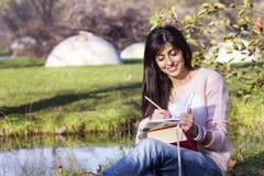 Escrita e leitura que da jovem mulher um livro em um outono estaciona Imagem de Stock
