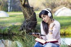 Escrita e leitura que da jovem mulher um livro em um outono estaciona Imagem de Stock Royalty Free