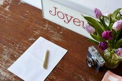 Escrita em tulipas do caderno e em decoração da câmera fotografia de stock