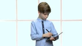 Escrita esperta do rapaz pequeno no dispositivo da tabuleta video estoque