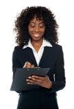 Escrita executiva fêmea africana no bloco de notas fotos de stock