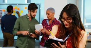 Escrita executiva fêmea no organizador e nos colegas que discutem no fundo