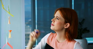 Escrita executiva fêmea sobre a nota pegajosa na placa de vidro filme