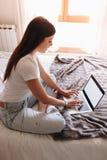 Escrita fêmea alegre no laptop genérico fotos de stock