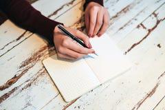 Escrita fêmea da mão na página Imagem de Stock Royalty Free