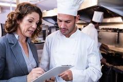Escrita fêmea do gerente do restaurante na prancheta ao interagir ao cozinheiro chefe principal imagem de stock
