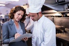 Escrita fêmea do gerente do restaurante na prancheta ao interagir ao cozinheiro chefe principal fotografia de stock royalty free