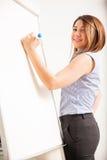 Escrita feliz da mulher de negócios em uma placa Imagens de Stock